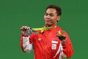 Indonesia's Eko Yuli Irawan poses with his silver medal on the podium of the Men's 62kg weightlifting competition at the Rio 2016 Olympic Games in Rio de Janeiro on August 8, 2016.  / AFP PHOTO / GOH Chai Hin